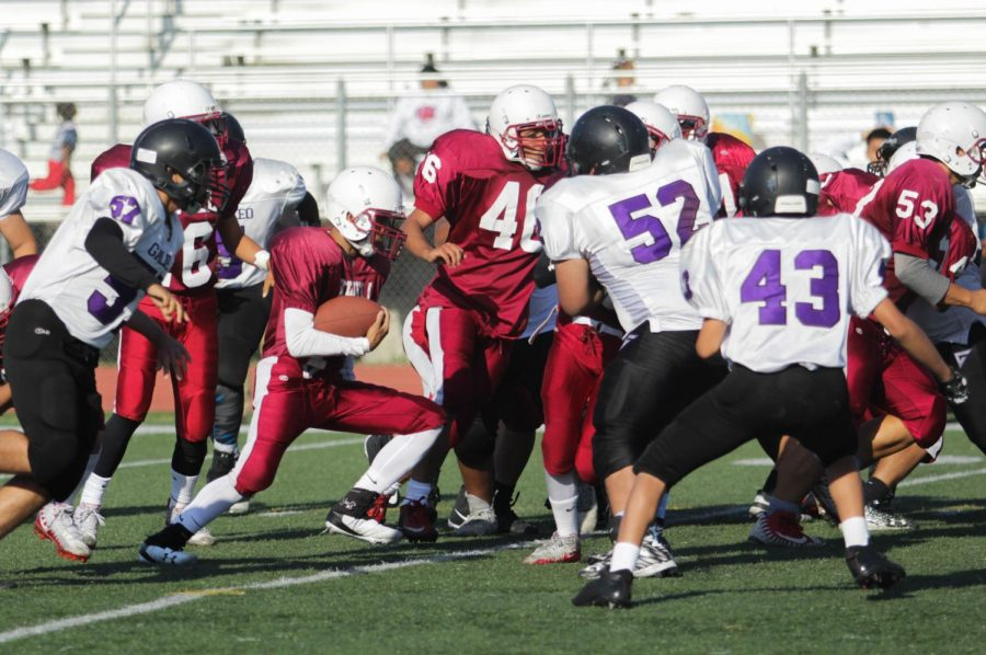 Freshman Adrian Navarro carries the ball avoiding Lion defenders