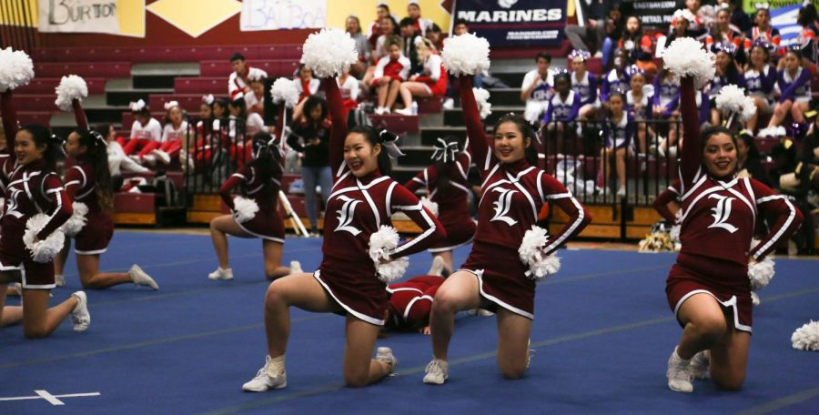 Freshman Alice Eng, juniors Gigi Huang and Darcy Munoz hold up their pom-poms at the end of their dance routine.