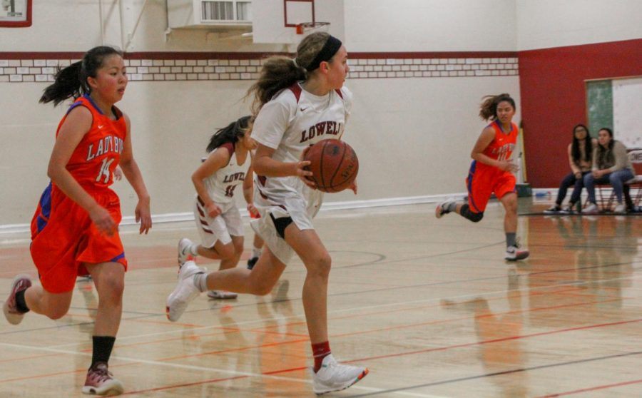 Freshman point guard Elle Ladine strives to drive down the court toward the  opponents' basket.