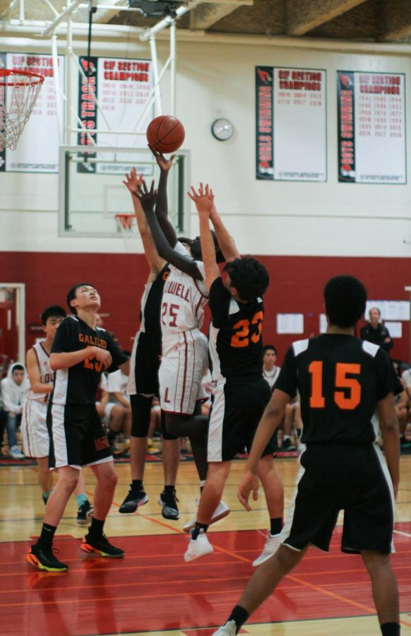 Sophomore forward Kevin Silvestro lays up the ball in midst of two Lion defenders attempting to block him.