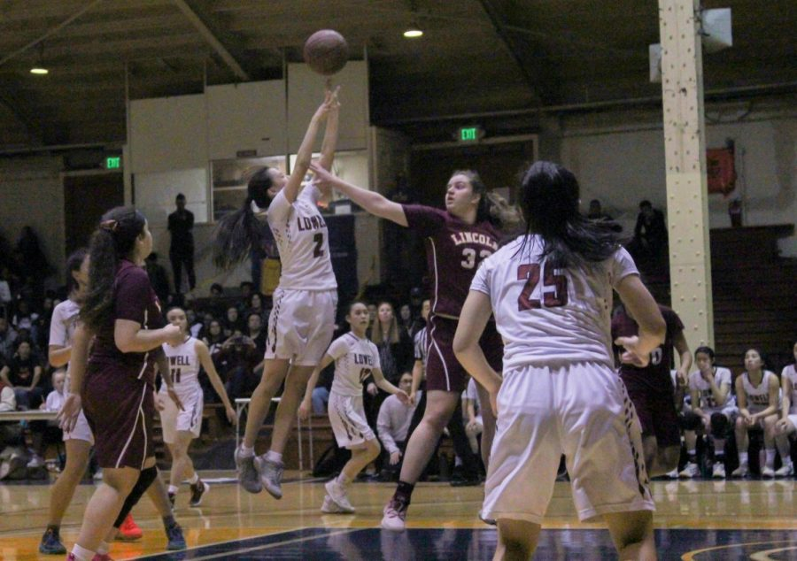 Senior KD Lee takes a shot at the basket as a Mustang tries to block her.