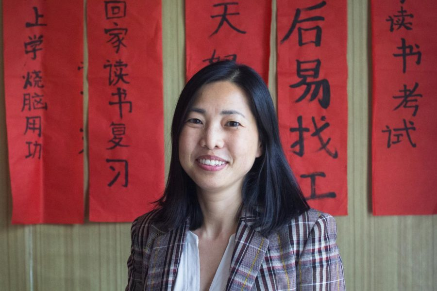 Chinese teacher Jian Liang stands in front of Chinese New Year scrolls that her students wrote to celebrate the holiday.