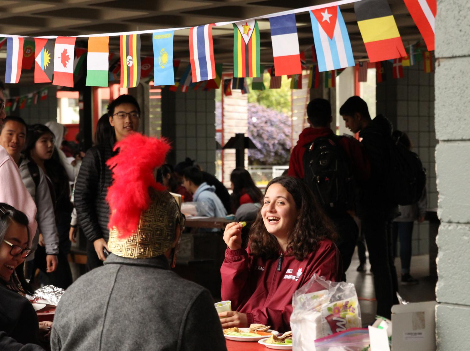 Students enjoy Globefest beneath international flags.