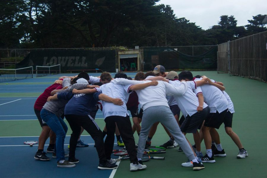 The team, continuing their tradition, huddle in a circle after defeating the Mustangs.