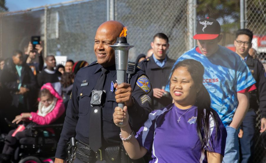 SFPD policeman and Special Olympics participant held the Olympic torch together during the opening ceremony.