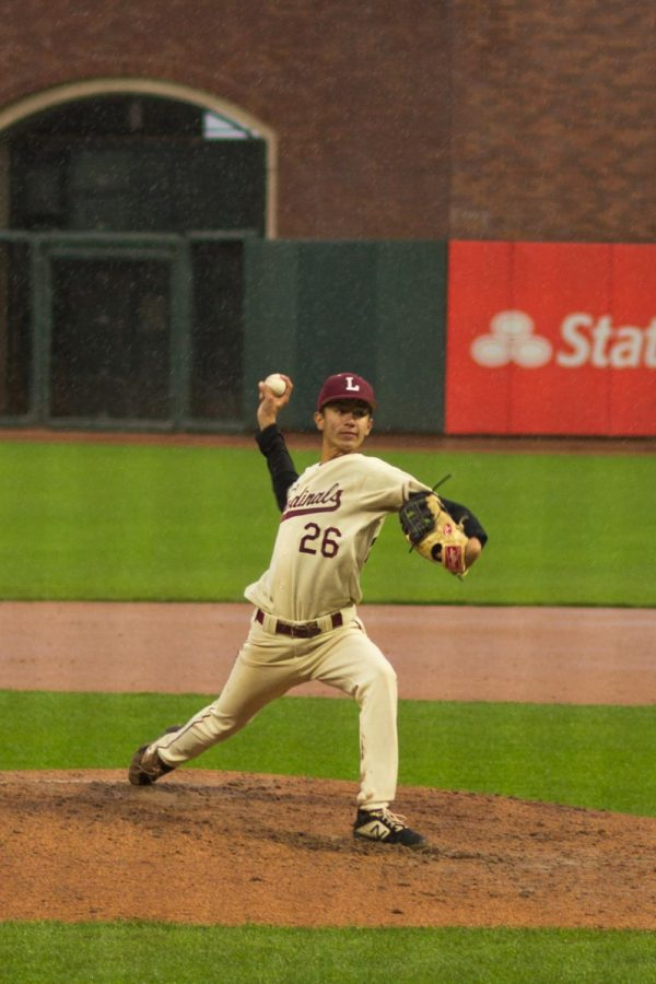 Taking an upright stride, sophomore infielder and pitcher Jack Schonherr prepares to throw a fastball atop the mound.