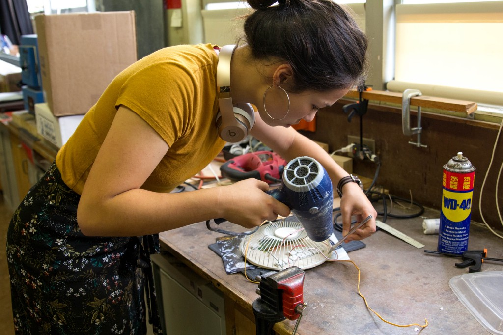 Junior Abigail Falk works on a wearable sculpture made of discarded electronics.