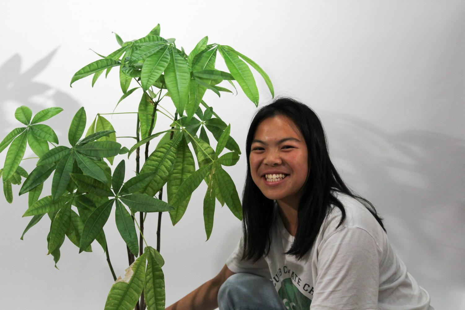 ECO Club president Kristen Tam poses by a plant