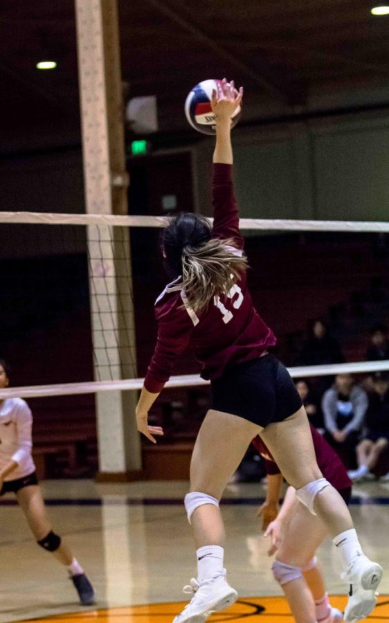 Senior outside hitter Eunice Go leaps up for an aggressive spike at her opponents.