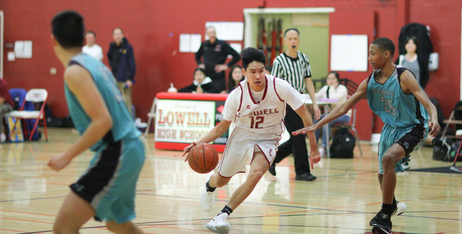 Sophomore forward Derek Quach fiercely dribbles down the court during the game against the Burton Pumas on Jan. 14 at home.