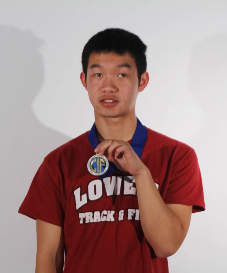 Junior Ethan Fung, in his Cardinal-spirited Track & Field shirt, proudly holds his medal in front of his chest.