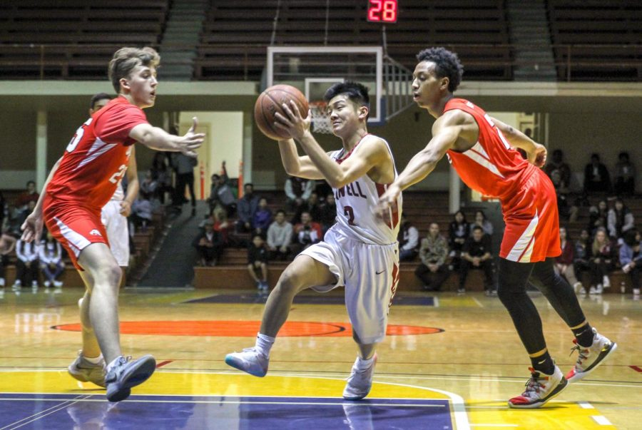 Senior guard Joshua Ng dodges two Eagle defenders as he makes his way to the hoop.