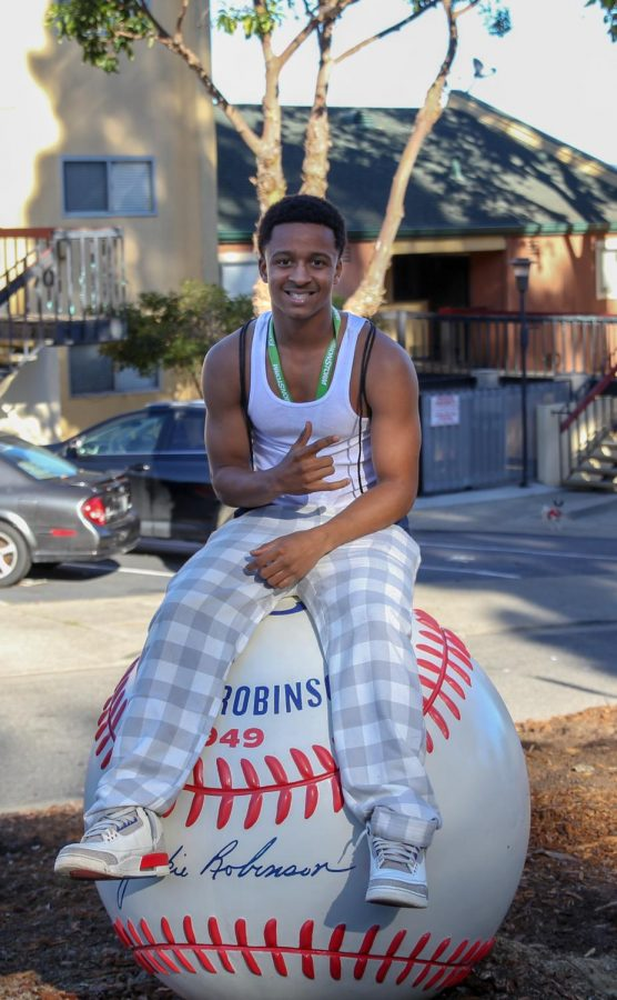 Darius Heckard sits atop a sculptural tribute to Jackie Robinson, the first African American to play in Major League Baseball.