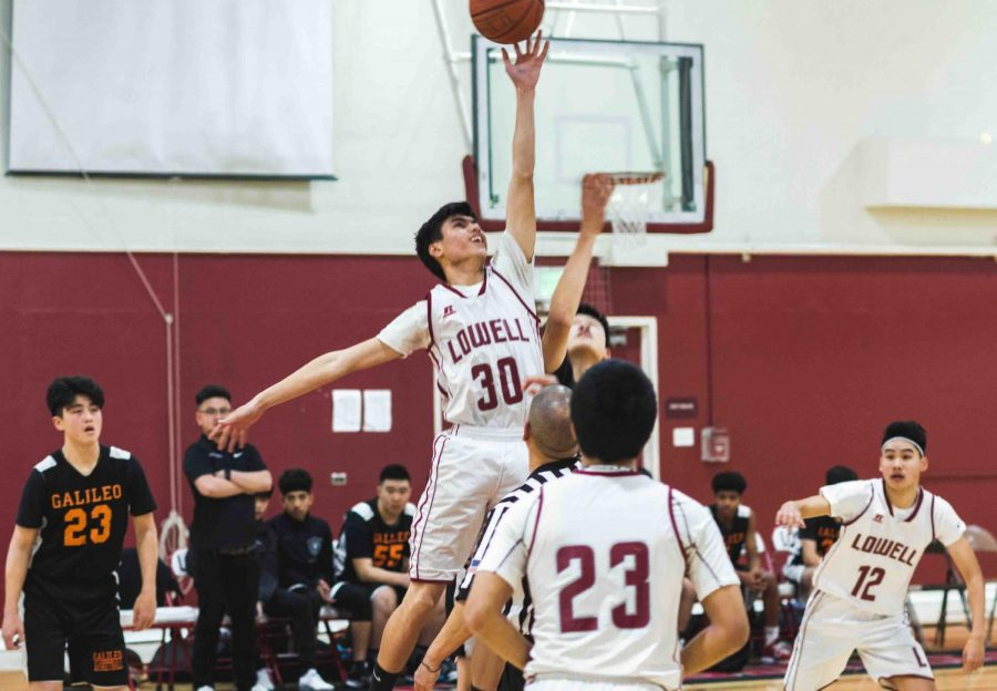 Sophomore forward Jeremiah Hizon jumps up and gets the ball in the tip off against the Galileo Lions at home on Jan. 31.