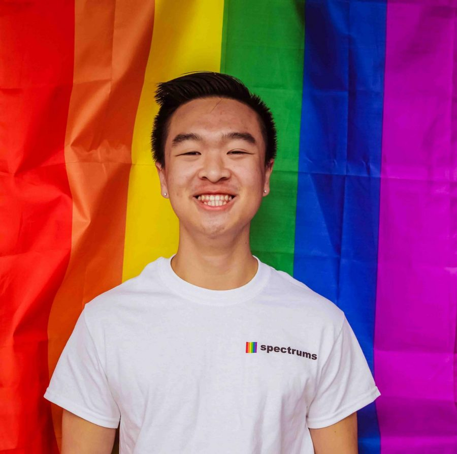 Senior Community Liaison Evan Chan stands in front of the rainbow flag. He identifies as queer.