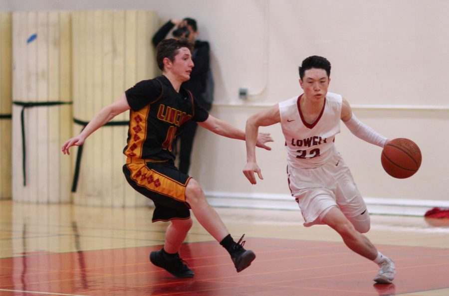 Agilely staving off from his opponent's defense, junior point guard Nathan Ly dribbles furiously down the court.