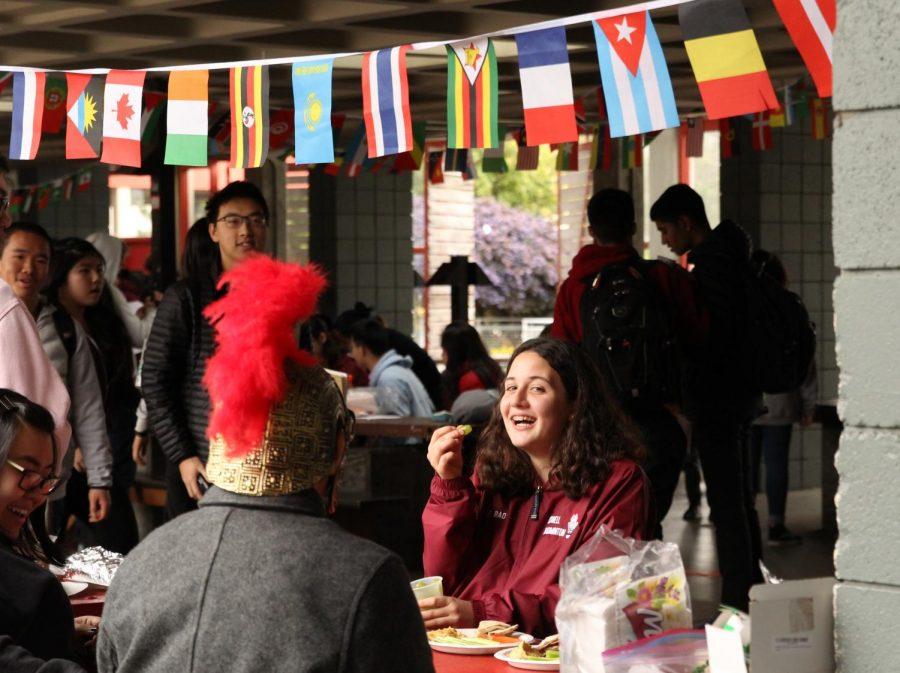 Students enjoy Globefest beneath international flags.