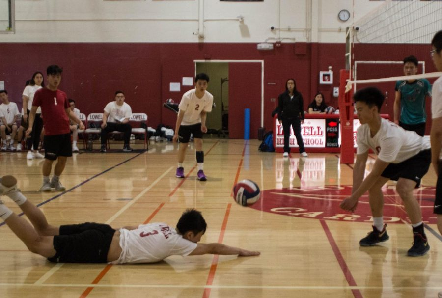 Junior right side hitter George Pan dives with a roll to save the ball.