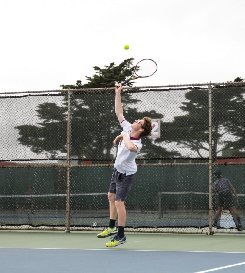 Senior co-captain Nick Morgenstein serves the ball after blessing the tennis court using Virgin Mary candles.